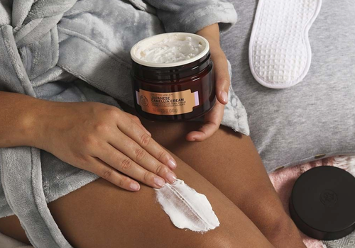 woman applying body shop japanese camellia cream to her legs