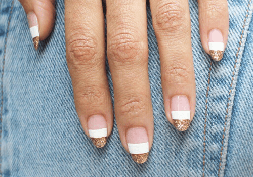 gold and white block stripe nail design against denim background