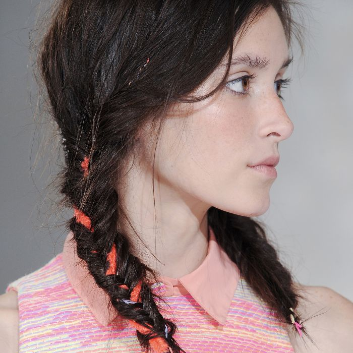 Woman wearing braided pigtails with ribbons