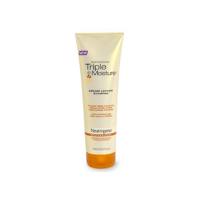 Cream colored tube of shampoo with an orange cap on a white background.