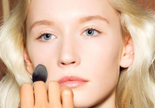 Model with clear skin getting her makeup done