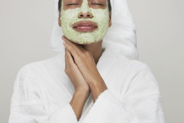 young woman in a robe wearing a face mask