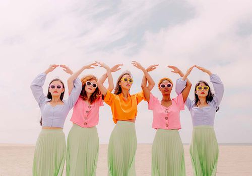 group of femmes on the beach in colorful outfits
