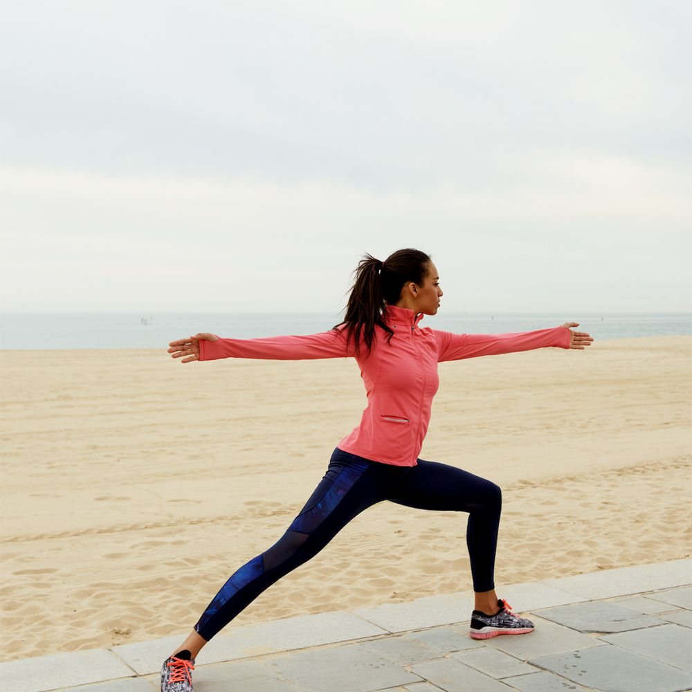 person doing exercise lunge on beach