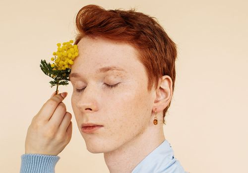 person holding flower with eyes shut
