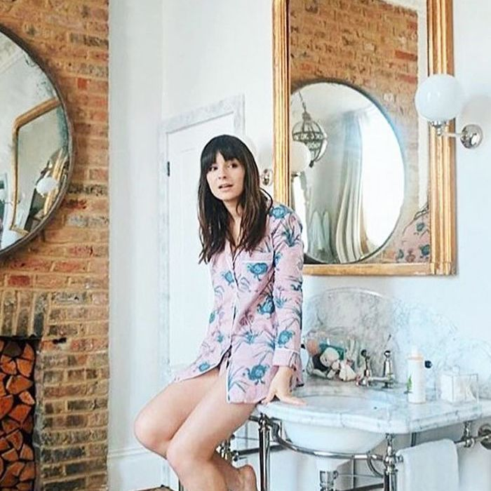 Influencer Liv Purvis wearing pajamas and sitting on a bathroom sink