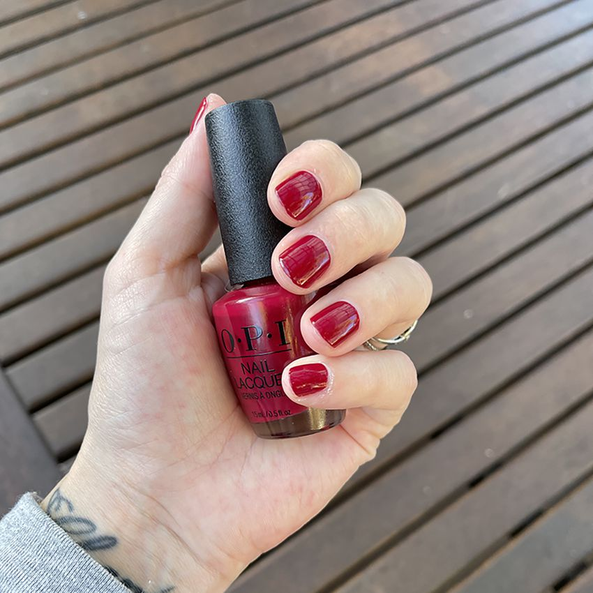 The author holds a bottle of OPI's Malaga Wine nail lacquer, with her nails painted