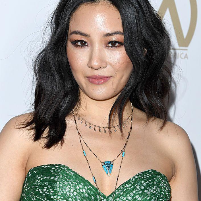 Constance Wu with wavy, medium-length hair
