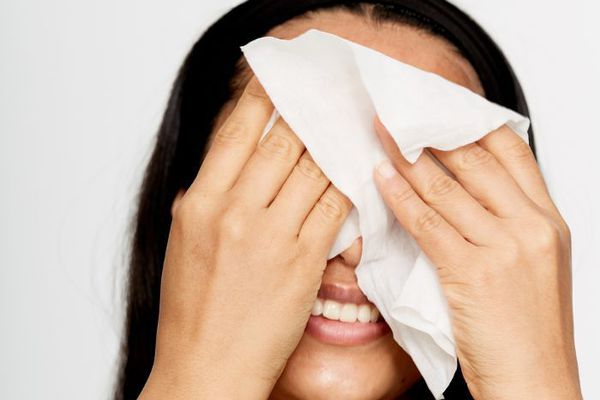 Woman wiping face with tissue