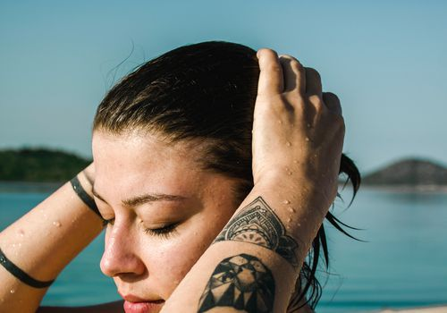 girl with wet hair near a body of water, with tattoos on both arms