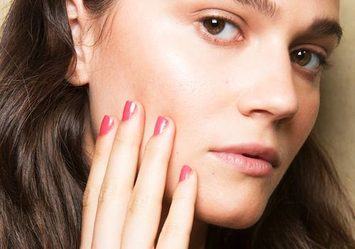 model with pink nail polish touching her face