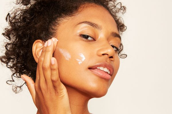 mixed girl applying creme to face