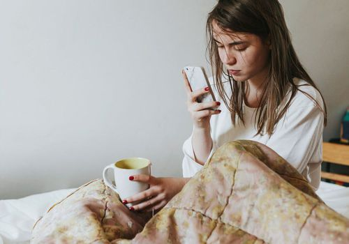 A young woman in bed on her phone and holding mug.