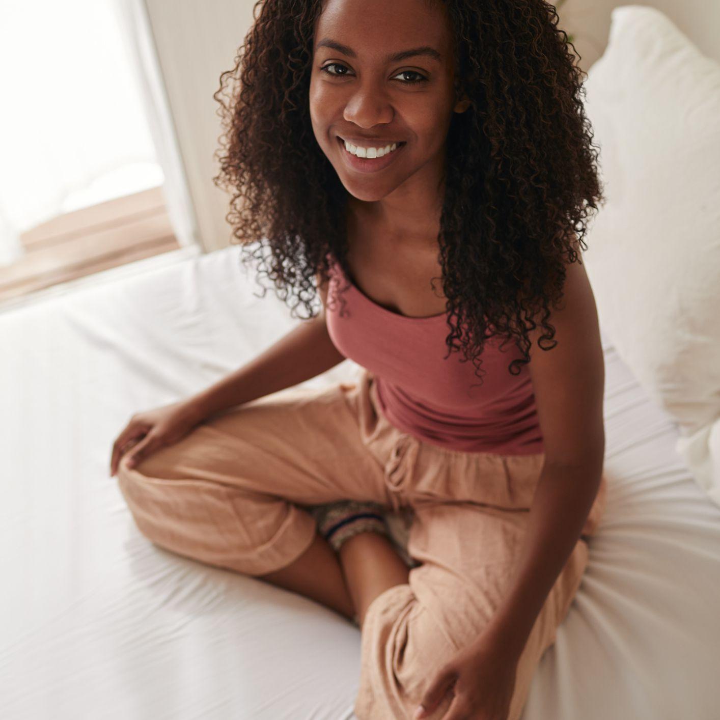 Черная женщина занимается йогой на кровати