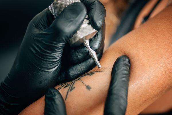A tattoo artist giving someone a tattoo