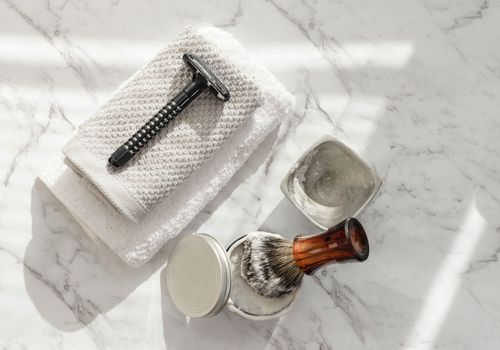 Close-up of shaving equipment on a marble table