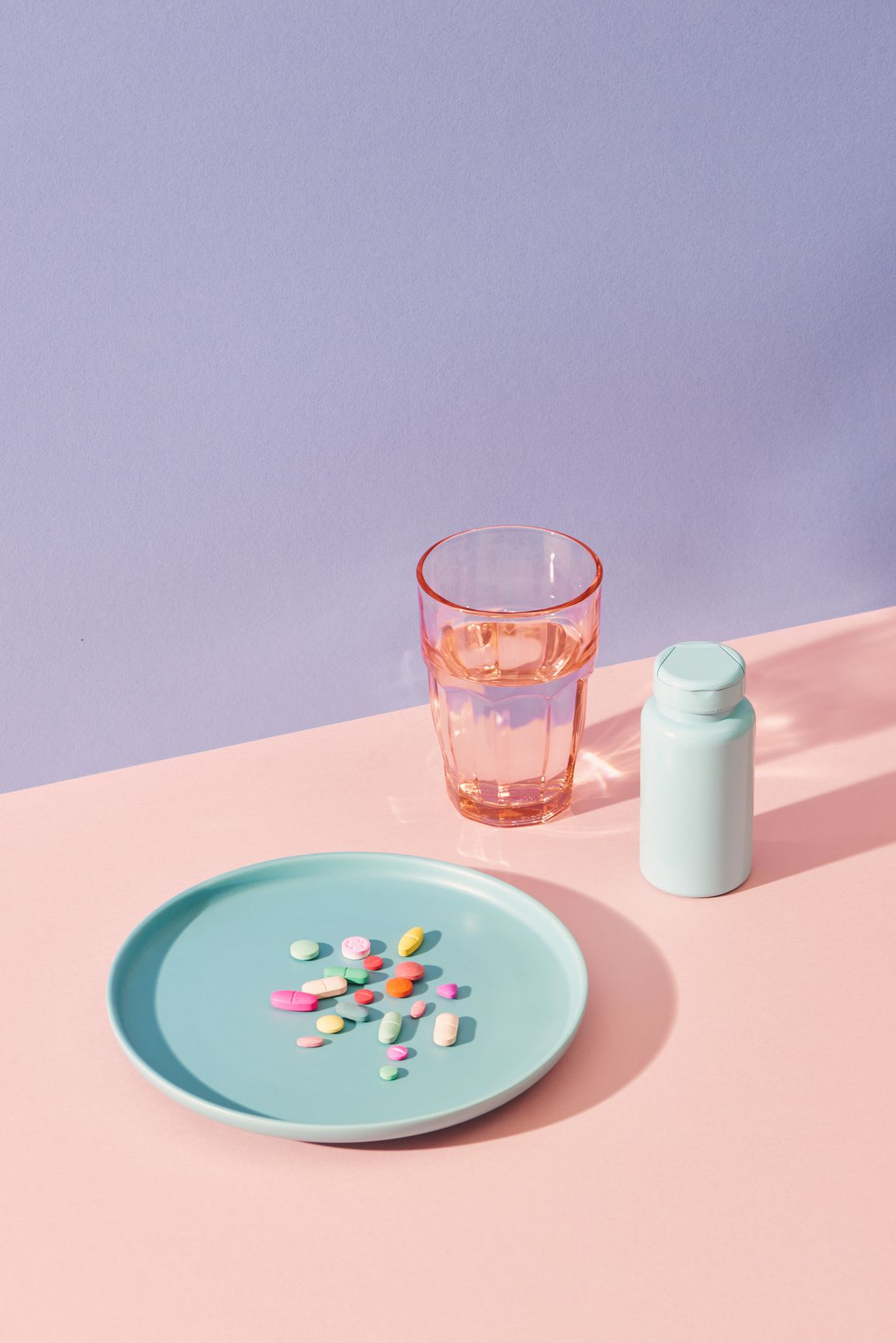 vitamin supplements on table with glass and pill bottle
