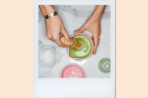hands mixing matcha with a wooden whisk
