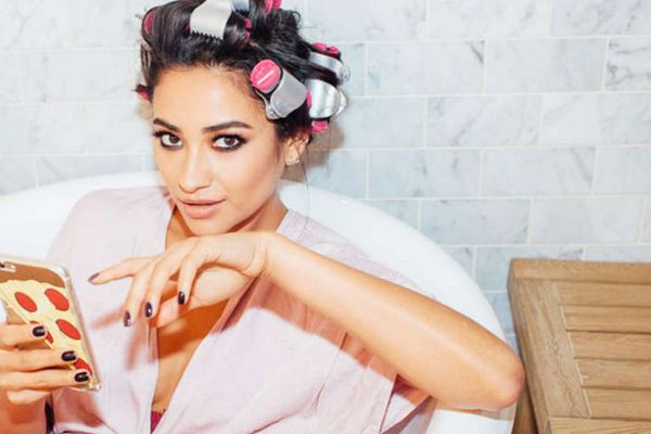 Actress Shay Mitchell sitting in a bathtub with her hair in curlers