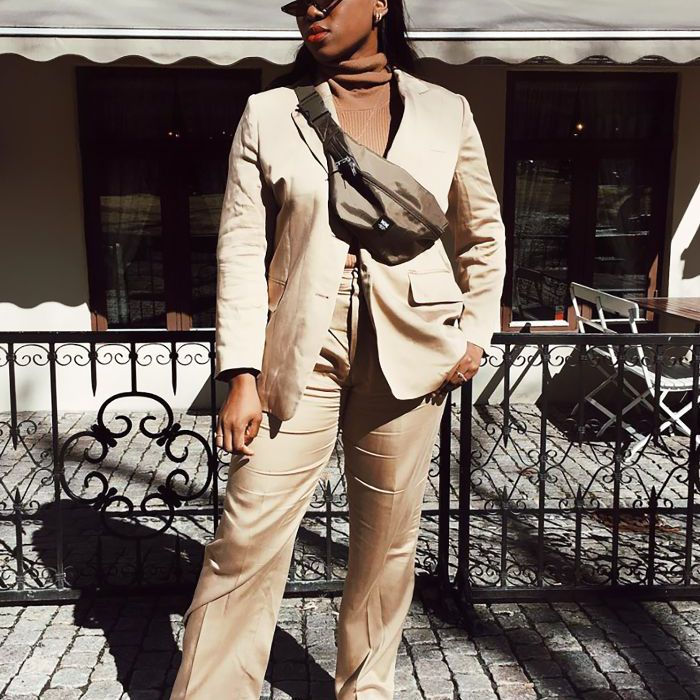 Young woman wears a turtleneck with a suit and sneakers