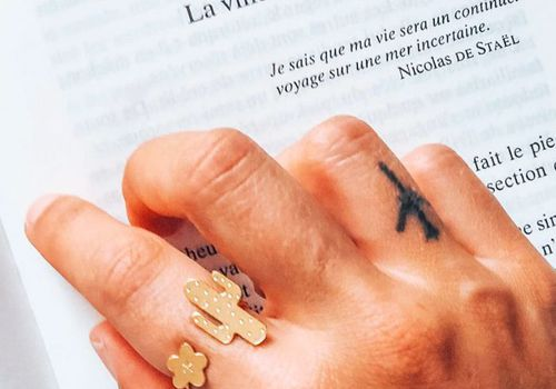 Woman's tattooed hand resting on book