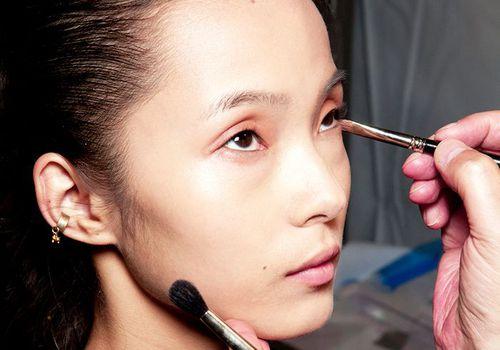 Makeup artist applying eye makeup to model