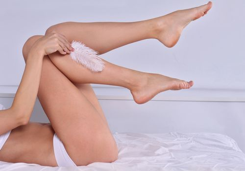 Woman running a feather over her legs