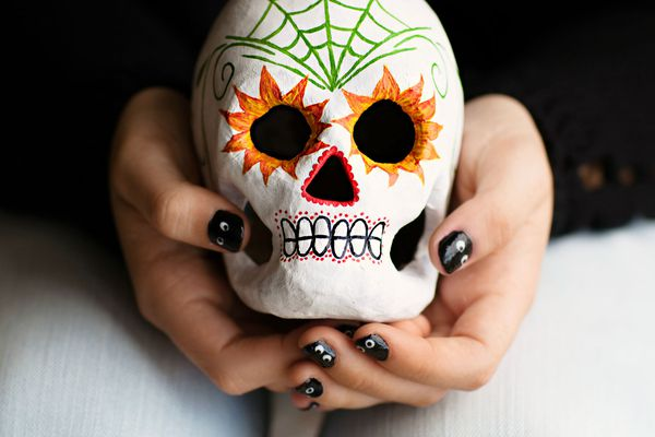person holding a sugar skull head in her hands