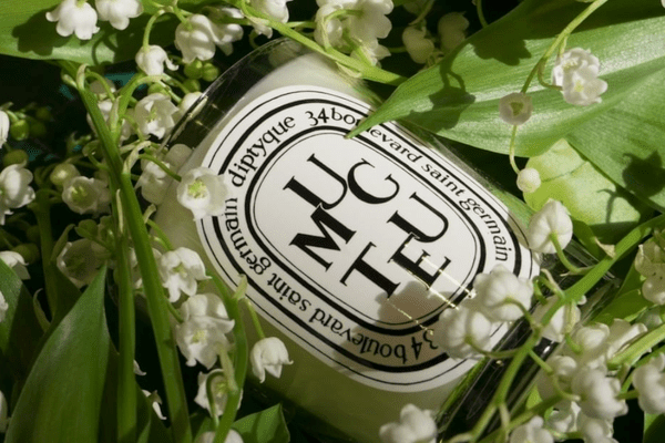 diptyque candle on bed of flowers