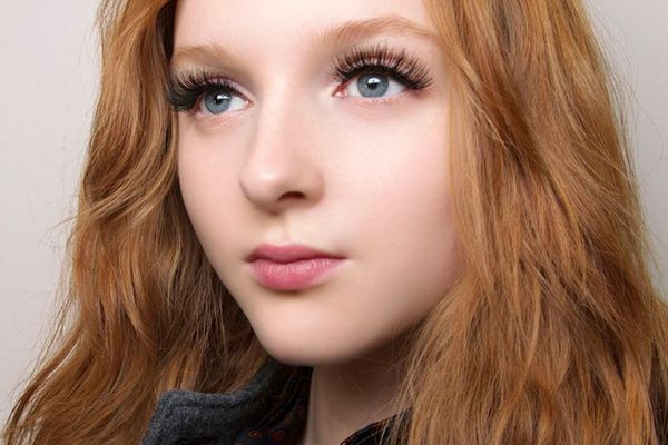 Woman with wavy, red hair and long eyelashes