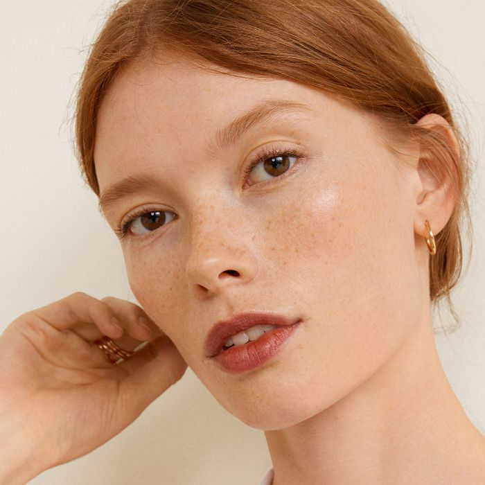 Best Drugstore Lipstick: Woman with gold jewellery and red hair