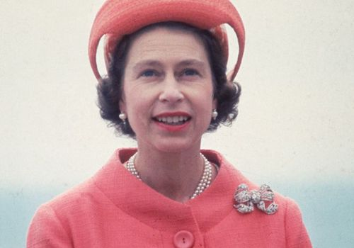 the queen in a coral jacket and lipstick
