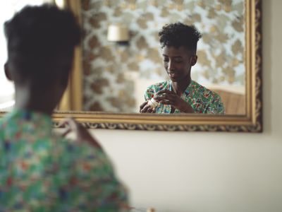 A woman looking at a face cream reflected in a mirror.