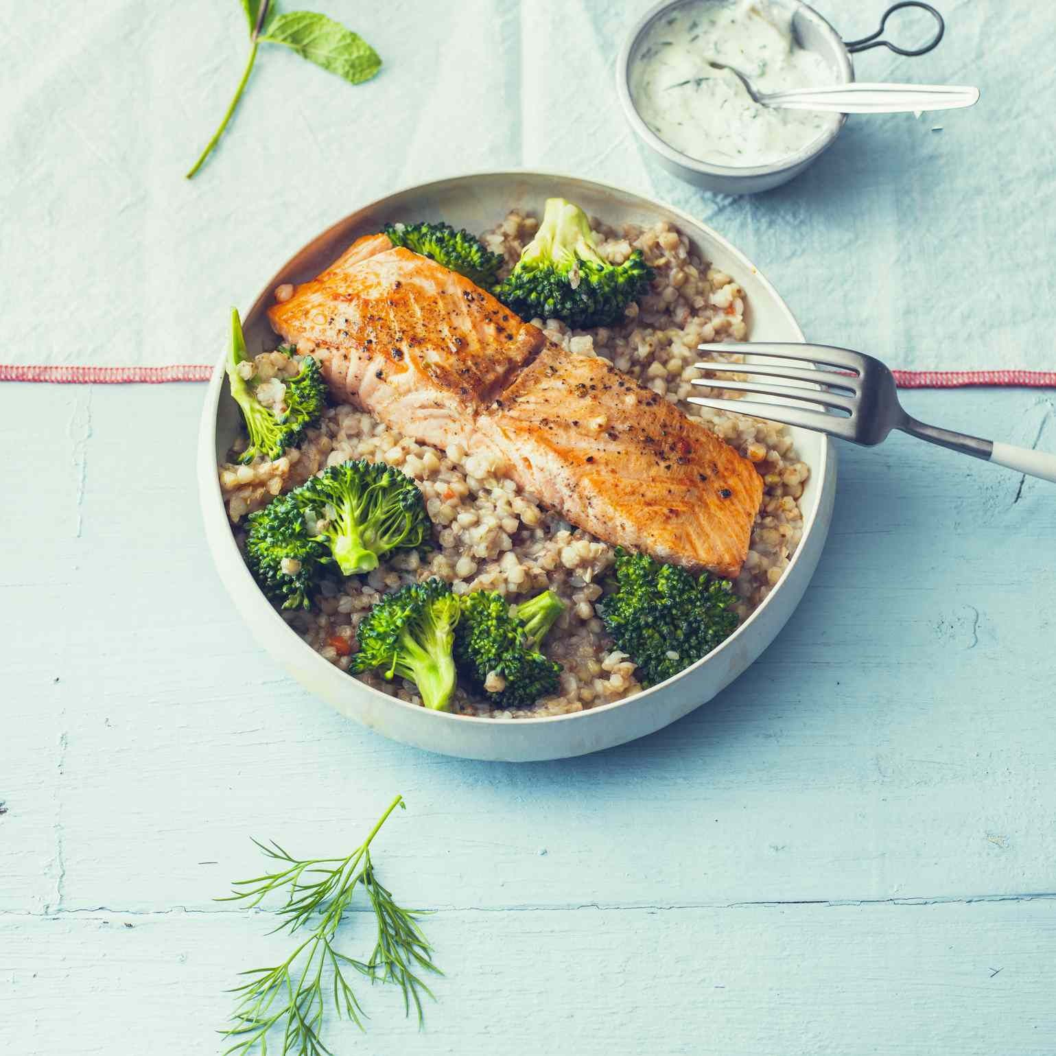 salmon with buckwheat pilaf and broccoli in a bowl