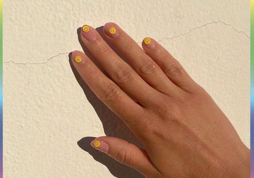 smiley face yellow nail design