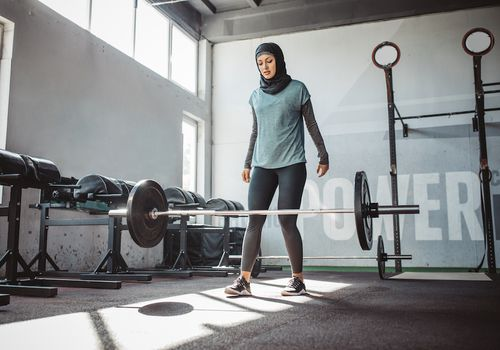 Woman in a gym, having just dropped weight bar with dumbbells