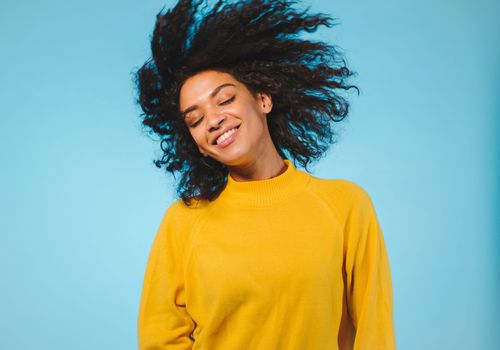 Black woman shaking her hair against a blue background