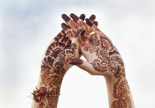a woman's hands covered in henna tattoos facing towards the sky