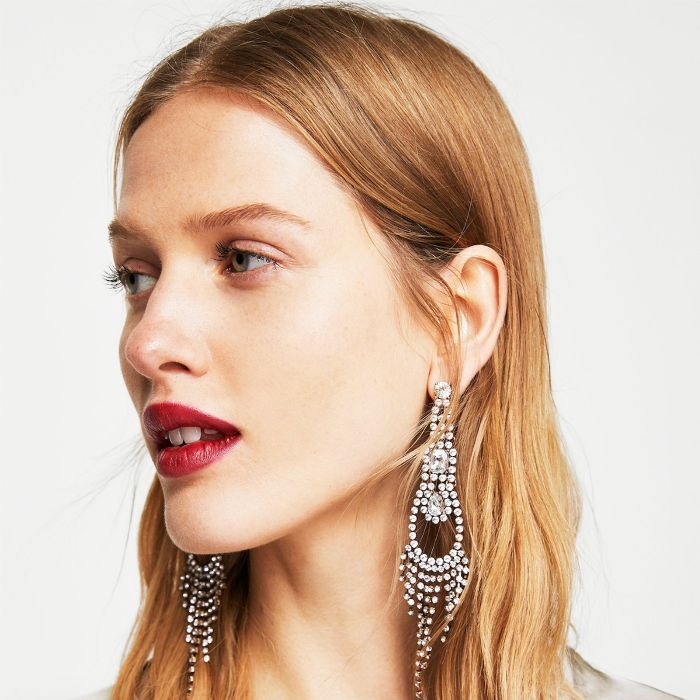 Best Anti-Ageing Serum: Woman with red lipstick and crystal earrings