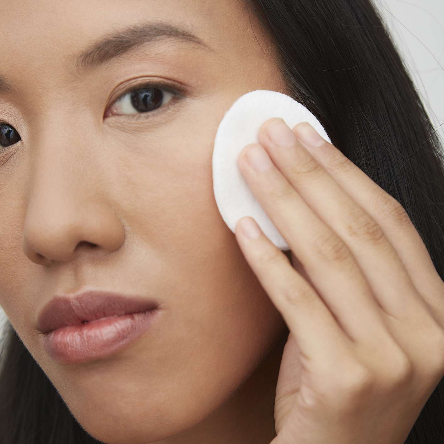 woman removing makeup with a cotton round