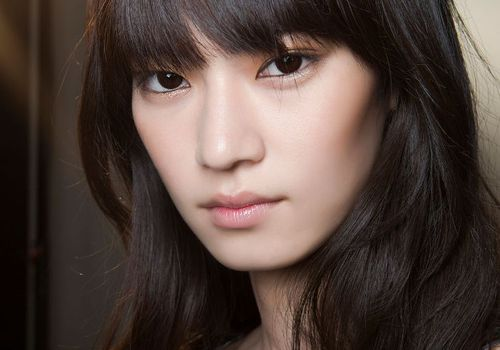 model with dark hair and bangs