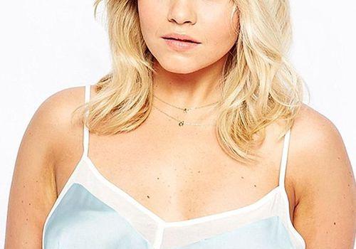 Blonde model wearing a blue camisole