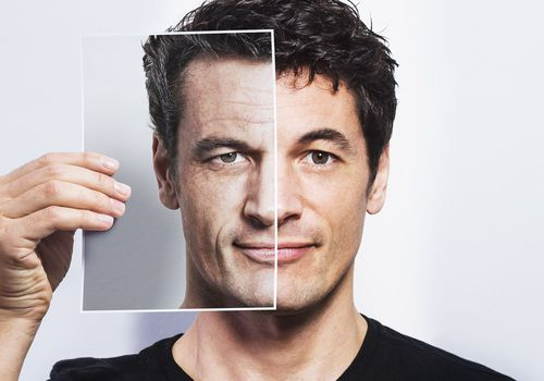 Man holding aged photo of himself over half his face