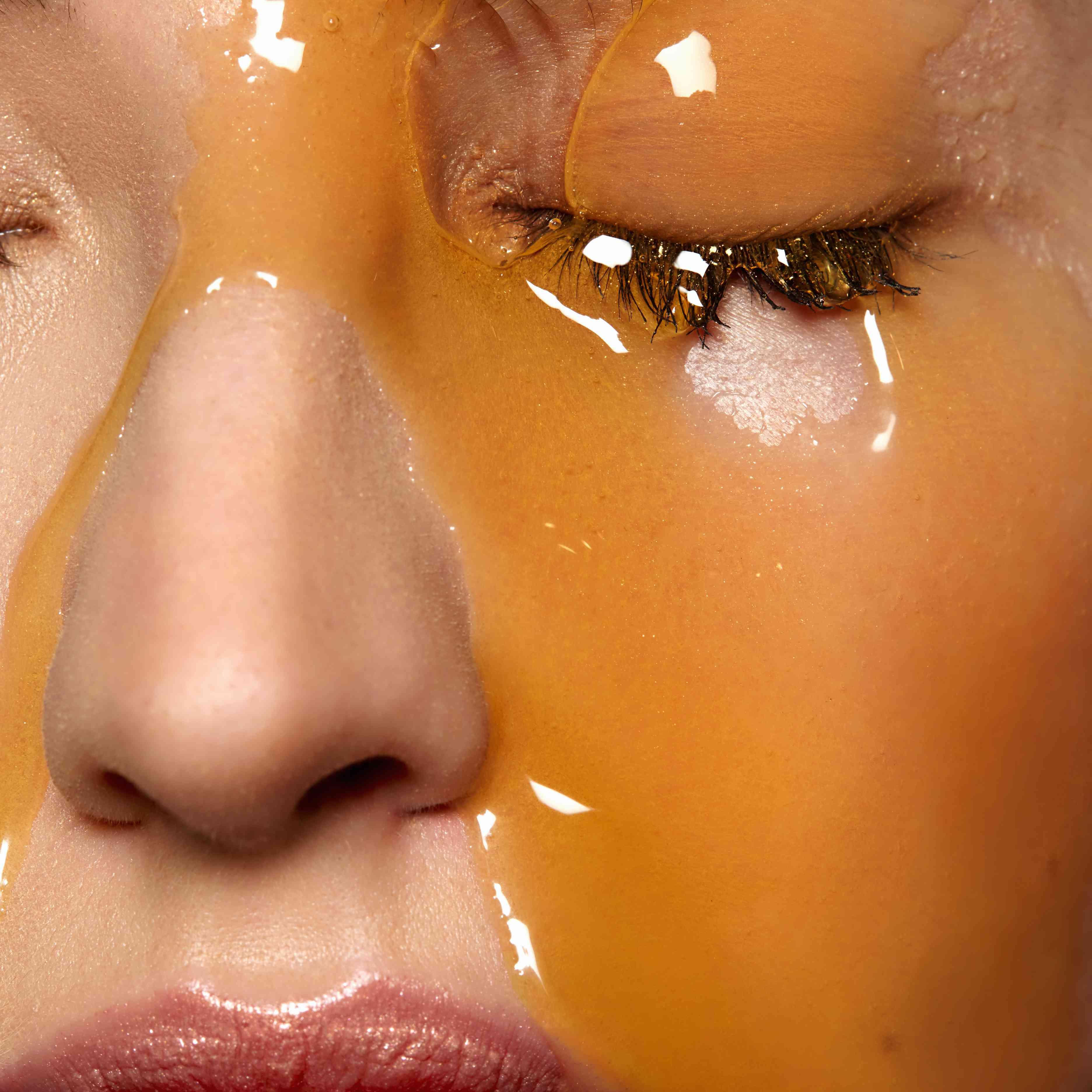Female models face covered in honey