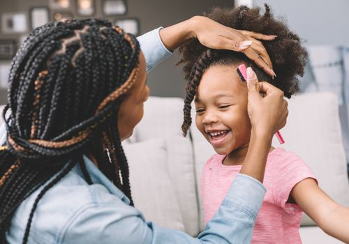 A woman flat twisting her daughter's hair.