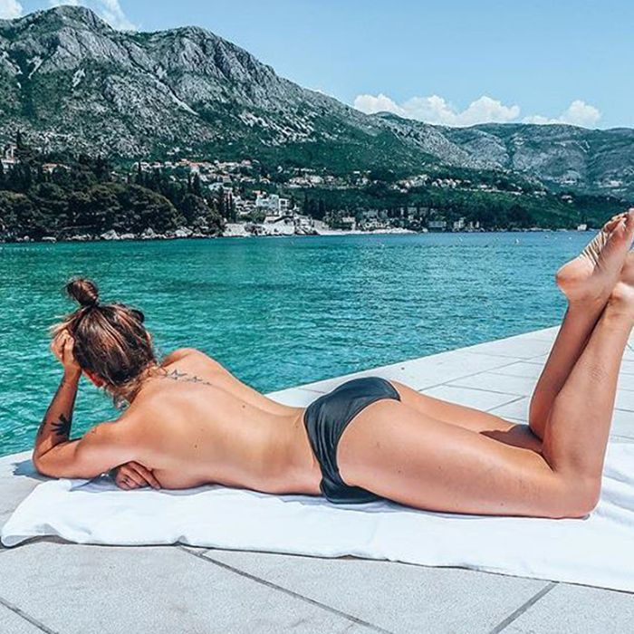 Topless woman laying on a beach towel by the water