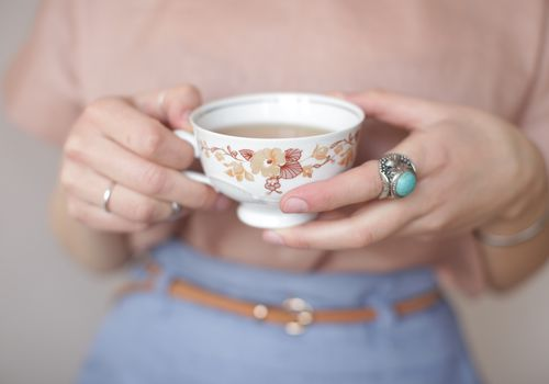 woman wearing blue ring holding tea cup