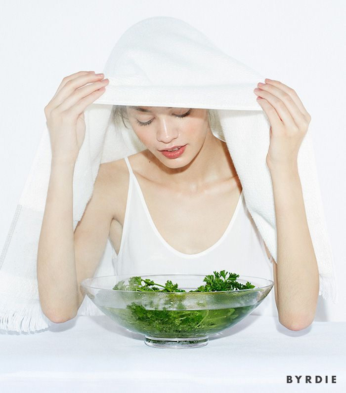model with bowl of herbs in water and towel on head