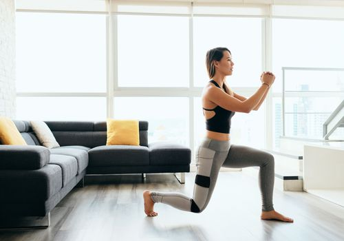 woman doing a lunge stretch in her living room