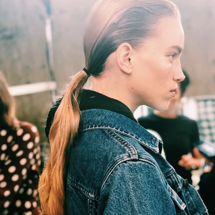 Model with hair slicked back into a ponytail